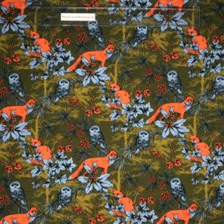 Bild Baumwolljersey Stoff in der Farbe olivgrün mit orangenen Füchsen, blauen Eulen und Pflanzen