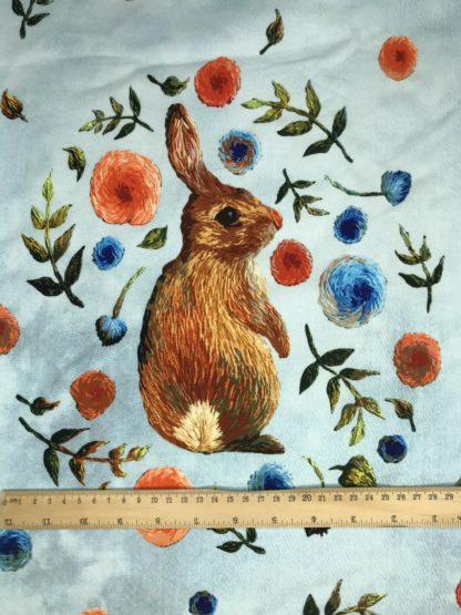 Bild Baumwolle Jersey Panel in hellblau meliert mit braunem Hasen, grün, orange, blau Blumen, grüne Blätter